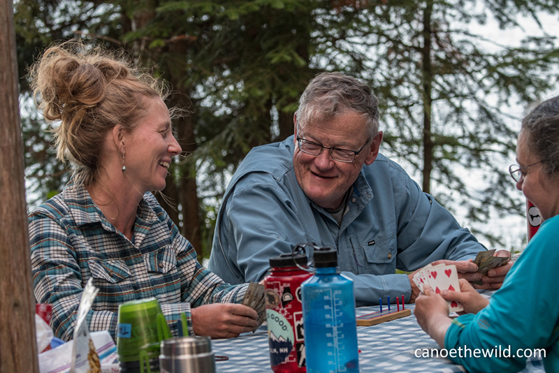 Maine guide Tammi Matula playing cards with canoe guests after a day's paddle and hearty meal.